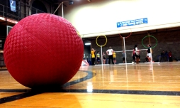 A dodgeball is used as a bludger in Quidditch Club. The club practiced in Stansbury Hall on Feb. 5 and is seen stretching before practice by the goal hoops.