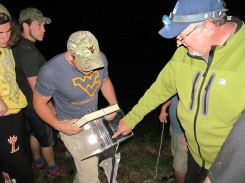 Dr. Kyle Hartman, right, points out where the larvae can swim into the trap. Ed Olesh, left, holds the larvae trap. PC: Jillian Clemente